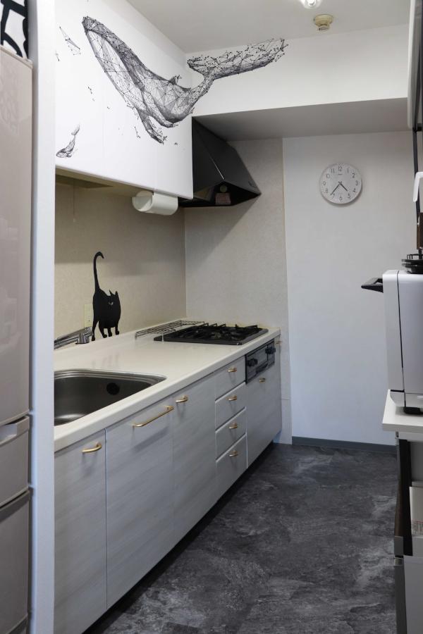 キッチンシステムキッチンは木目、上棚扉は白を施工